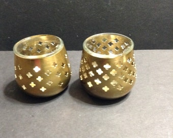 Pair of brass votive candle holders, with a cut-out design, with two glass votive holders to fit inside.