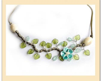 Flower necklace with spring green turquoise ceramic and green leaves.