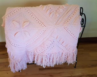 Pink knitted afaghan, perfect for a baby or young girls room.