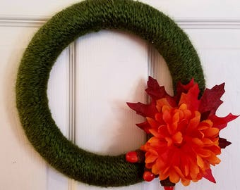 Green fall wreath with leaves and flowers