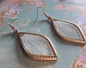 A pretty pair of earring gold white sewing thread