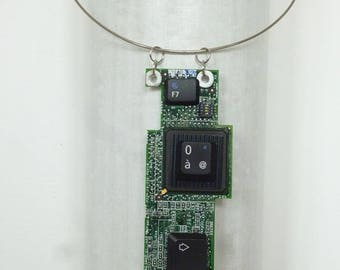 Pendant piece of electronics and keyboard keys.