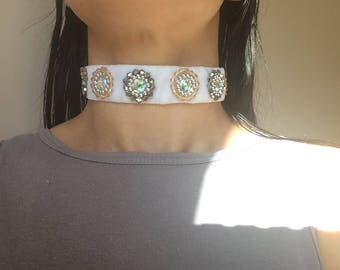 A beautiful white velvet choker with light orange and silver beads sewn around sparkly centre gems.
