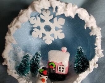 Christmas diorama ornament with clay house, snowman and winter scene.