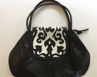 Black leaf tooled leather handbag with white accent color