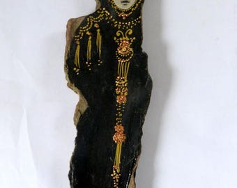 Talisman statuette on a driftwood in black and gold.