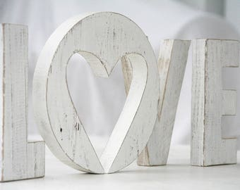 LOVE inscription with wood retrieval letters of e or with heart shaped hole