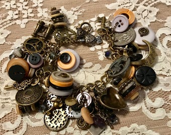 Bracelet Loaded with Buttons And Charms .   Antique Bronze Tone Bracelet  With  Black, Gray, Taupe And Neutral Colored Buttons.
