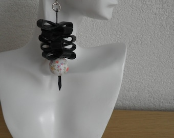 Earrings of black rubber with a bead with flowers.Recycled and original art.The earrings are 3,15 inches long.The earrings are handmade.