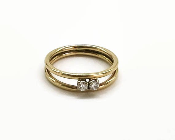 Diamond ring in 9 carat yellow gold setting, 2 small diamonds, 2 circular bands that join at back, 16PTS of diamonds, size L.5 / 6,  1977