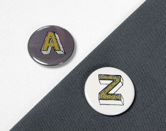 Letter button badges, alphabet & numbers, personalised initial pin jewellery, 25mm/ 1 inch. Juniper Red font. Word lover