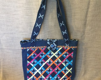 Carrier bag in denim, indigo fabric and multicolored ribbons.