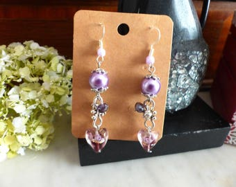 A pair of dangle earrings with heart glass
