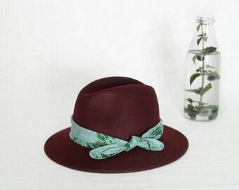 Burgundy fedora hat decorated with a batik scarf