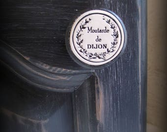 A piece of furniture (door or drawer) wood and ceramic button: Dijon mustard