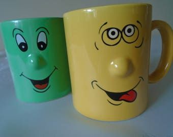 face mugs x 2 pale green and yellow.