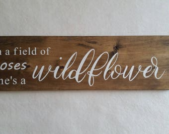 In a field of roses she's a wildflower wooden painted sign; white text