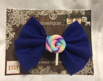Dark blue cotton hair bow with clay spiral Lolly center. On alligator clip.