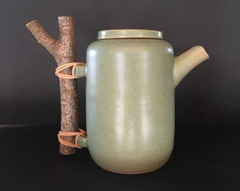 Ceramic tea pot with wooden handle and leather detail