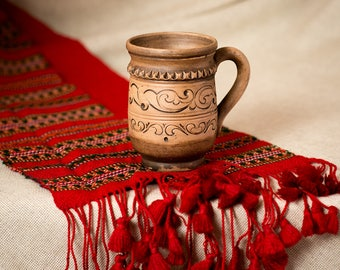 Ceramic pottery coffee mug in traditional style with natural clay texture
