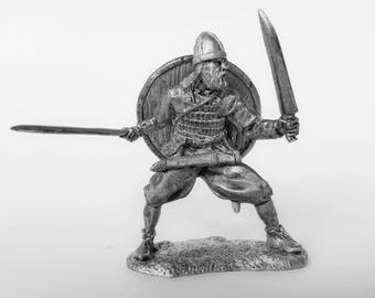 Tin soldier. Tin miniature. Pewter sculpture. Vikings. Viking with two swords. The scale is 1/32.