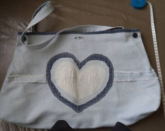 very light blue denim with embroidered initials M and B handbag on white canvas