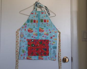 Children's reversible apron with front pocket, blue breakfast and penguin themed fabric