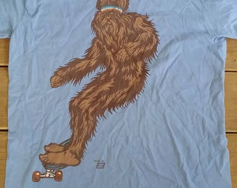 Ames Bros. Sasquatch / Bigfoot on Skateboard with Red, White and Blue Sweatband t-shirt Blue Men's Size Large American Yeti Cryptozoology