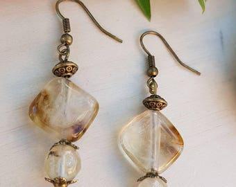 Gemstone beads earrings bronze beige tourmaline amber on metal stand.