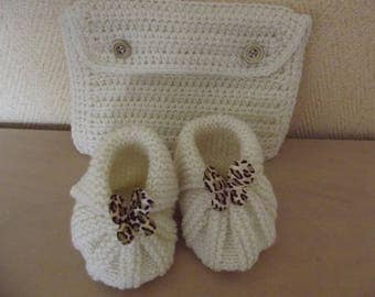with its matching pouch hand knitted ecru baby booties