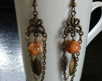 Earrings in orange Ocean jade beads, chandelier, bronze chain and feather charm mounted on hooks