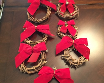 9 little handmade vine wreath ornaments with a red bow