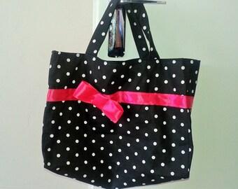Small tote bag in black fabric has white dots and fuchsia Ribbon