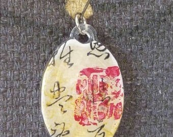 Resin oval pendant with Chinese motif
