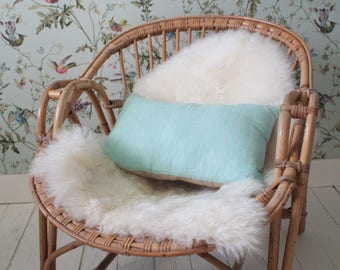 Small blue cushion with green PomPoms