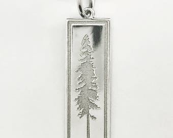 Silver colored aluminum pendant featuring a deep engraved pine tree design and Black leather cord necklace
