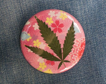 Pressed Cannabis Leaf Button on Bright Pink Background