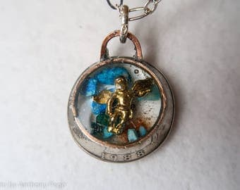 Gold cherub set in hand hammered year 1988 US quarter pendant featuring turquoise shards and Oklahoma red dirt