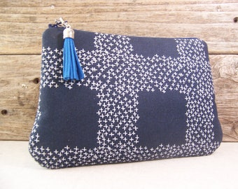 Clutch or Cosmetic bag in a modern navy blue fabric with a blue tassel has a waterproof washable lining - Make up bag or cosmetic bag.