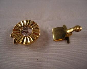 Round gold tone metal with Rhinestone clasp