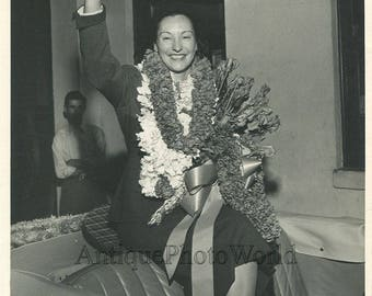 Woman with flowers waving in car vintage photo