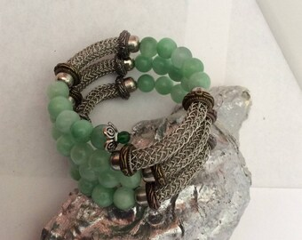wrapped around green stones and silver chain