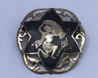 Vintage 6 point star sterling silver brooch with an engraving of woman pouring a jug.