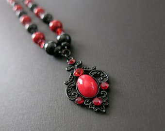 Red and black necklace with scrollwork pendant and earrings to match