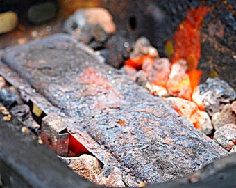 Burning coals on the bbq with orange flames with summer time lighting