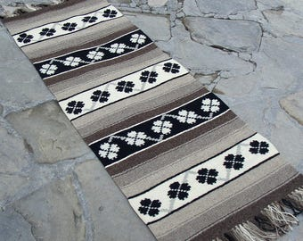 Handwoven wool rug in natural wool colors - white and grey/brown with white and black motifs