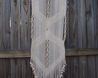 Cream macrame wall hanging with natural beads & shells.