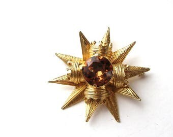 signed Benedikt NY brooch, large gold tone starburst and crown brooch with topaz glass