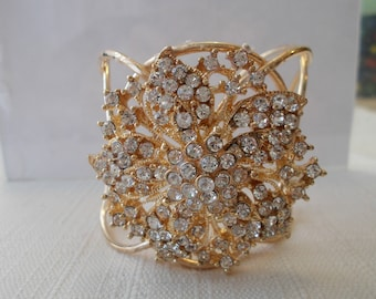 Gold Tone Cuff Bracelet with a Gold and Clear Rhinestone Center