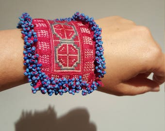 Bracelet with leather bottom, Center piece of fabric hmong embroidered in pink and beads ribeteando the piece.